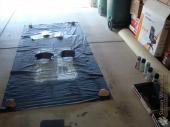 Spray painting setup - cheap plastic tablecloth weighed down with rocks in the garage