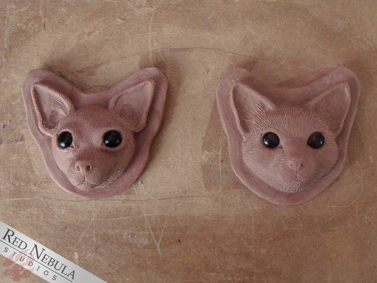 Cat and chihuahua face sculptures